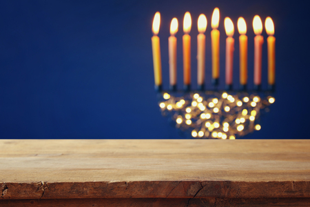 chanukiah: Empty wooden table in front of jewish holiday Hanukkah background with menorah (traditional candelabra) and burning candles Stock Photo