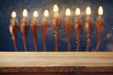 empty table: Empty wooden table in front of jewish holiday Hanukkah background with menorah (traditional candelabra) and burning candles Stock Photo