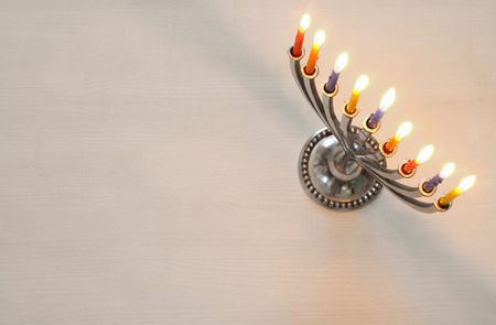 Top view Image of jewish holiday Hanukkah with menorah (traditional Candelabra). Selective focus Stock Photo
