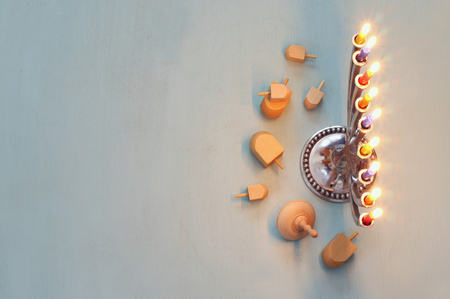 hanukah: Top view Image of jewish holiday Hanukkah with menorah (traditional Candelabra) and wooden dreidel (spinning top). Selective focus Stock Photo