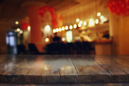 blurred background: Image of wooden table in front of abstract blurred restaurant lights background Stock Photo