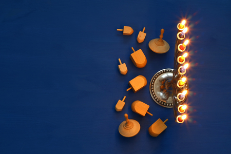 chanukiah: Top view Image of jewish holiday Hanukkah with menorah (traditional Candelabra) and wooden dreidel (spinning top). Selective focus Stock Photo