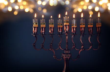 Low key Afbeelding van Joodse vakantie Hanukkah achtergrond met menora (traditionele kandelaar) en brandende kaarsen