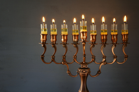 burning: Low key Image of jewish holiday Hanukkah background with menorah (traditional candelabra) and burning candles