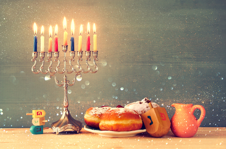 hanukiah: Image of jewish holiday Hanukkah with menorah (traditional Candelabra), donut and wooden dreidel (spinning top)