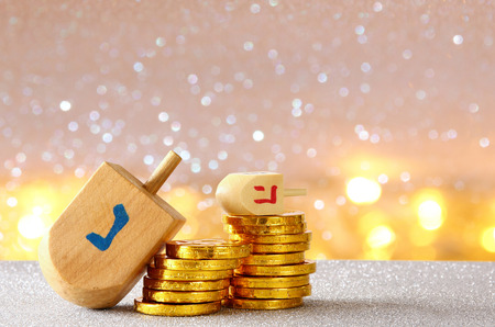 chanukiah: Image of jewish holiday Hanukkah with wooden dreidel (spinning top) and chocolate coins on the glitter background Stock Photo