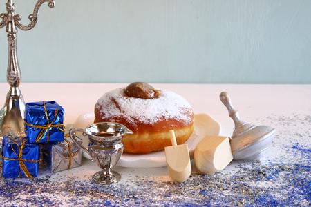 chanukiah: Image of jewish holiday Hanukkah, donut and wooden dreidel (spinning top)