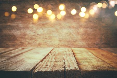 木製の素朴な背景にクリスマス温かみのあるゴールドのガーランド ライトの前で空のテーブルです。選択と集中