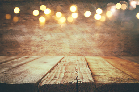 empty table in front of Christmas warm gold garland lights on wooden rustic background. selective focus Stok Fotoğraf