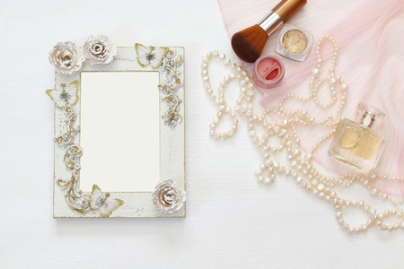 style woman: Top view image of vintage woman toilet accessory next to blank photo frame on the table