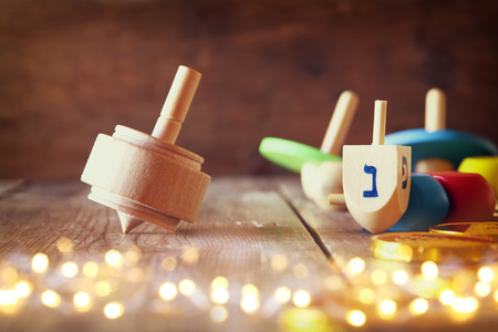 chanukiah: Image of jewish holiday Hanukkah with wooden dreidels colection (spinning top) and chocolate coins on the table