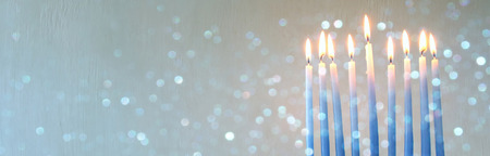 chanukiah: Image of jewish holiday Hanukkah background with menorah (traditional candelabra) and burning candles. Glitter overlay. Wide format