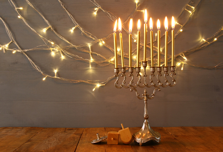 Low key Image of jewish holiday Hanukkah with menorah (traditional Candelabra) and wooden dreidel (spinning top). Vintage filtered