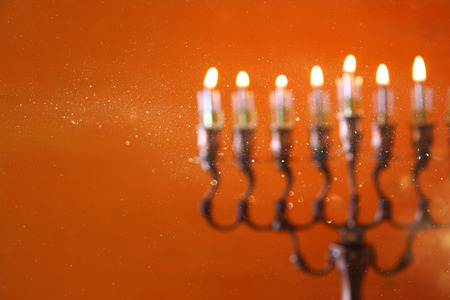 hanukah: abstract and blurry image of jewish holiday Hanukkah background with menorah (traditional candelabra) and burning candles
