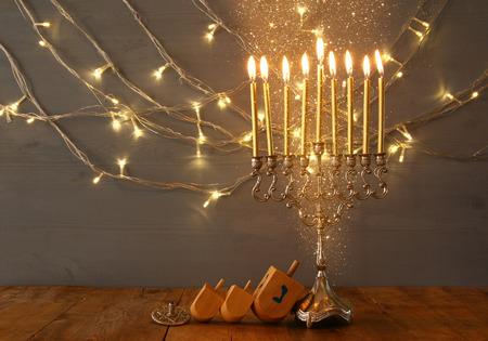 chanukiah: Low key Image of jewish holiday Hanukkah with menorah (traditional Candelabra) and wooden dreidel (spinning top). Vintage filtered