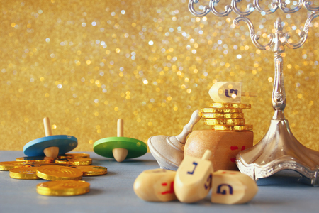 Image of jewish holiday Hanukkah with wooden dreidels colection (spinning top) and chocolate coins on the table. Selective focus