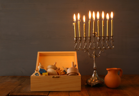 trompo de madera: Low key Image of jewish holiday Hanukkah with menorah (traditional Candelabra) and wooden dreidel (spinning top). Vintage filtered