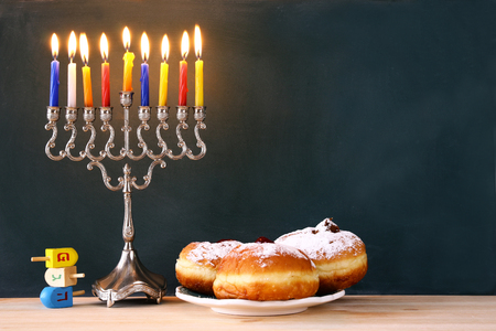 judaica: Image of jewish holiday Hanukkah with menorah (traditional Candelabra), donut and wooden dreidel (spinning top)