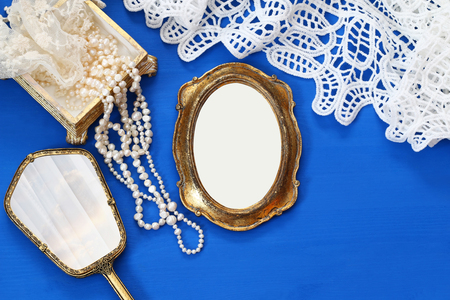Top view image of vintage woman toilet fashion objects next to blank photo frame on old wooden table. Ready for photography montage