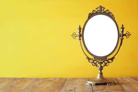 Oude uitstekende ovale spiegel staan op houten tafel. Stockfoto