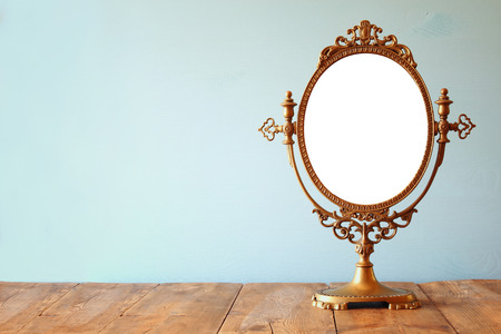 Vieux miroir ovale vintage debout sur une table en bois.