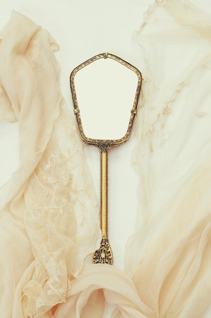 view an elegant wardrobe: Top view image of vintage hand mirror and lace scarf on white background. Can be used for photography montage Stock Photo