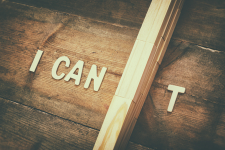 cant: Image of wall between letters I CANT, cutting the letter T so it written I CAN. Success and challenge concept Stock Photo