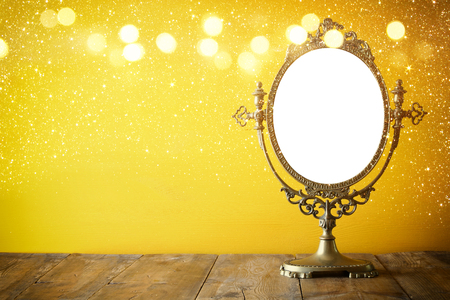 Old vintage oval mirror standing on wooden table. Vintage filtered with glitter overlay