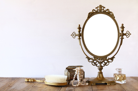 Old vintage oval mirror and woman toilet fashion objects on wooden table Stock Photo