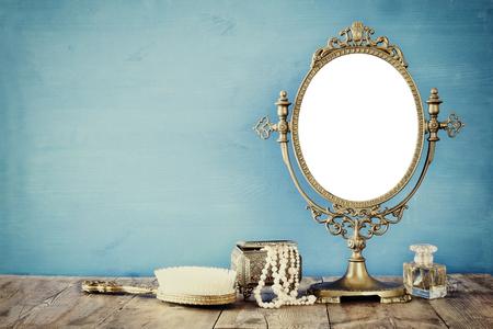 Oggetti vecchia annata ovale moda specchio e toletta della donna sul tavolo di legno. immagine filtrata Archivio Fotografico - 65829889