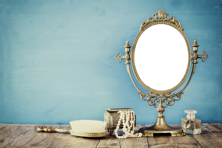 Old vintage oval mirror and woman toilet fashion objects on wooden table. Filtered image Stock Photo
