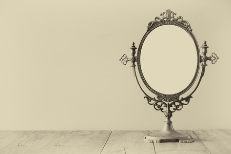 Old vintage oval mirror standing on wooden table. Sepia antique style filtered photo