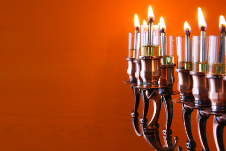 Selective focus image of jewish holiday Hanukkah background with menorah (traditional candelabra) and burning candles Stock Photo