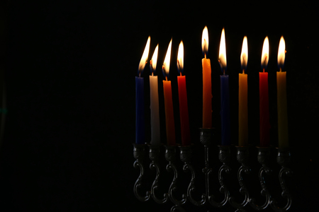 judaica: Low key Image of jewish holiday Hanukkah background with menorah (traditional candelabra) and burning candles