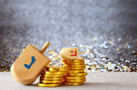 Image of jewish holiday Hanukkah with wooden dreidel (spinning top) and chocolate coins on the glitter background Stock Photo