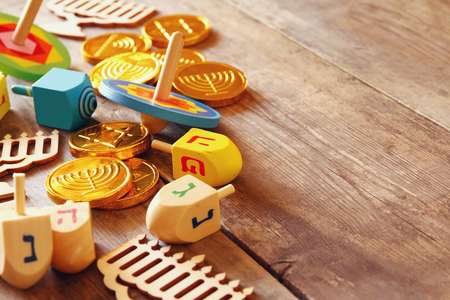 hanukka: Image of jewish holiday Hanukkah with wooden dreidels colection (spinning top) and chocolate coins on the table