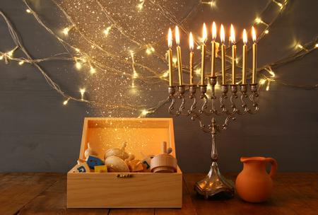 hanukka: Low key Image of jewish holiday Hanukkah with menorah (traditional Candelabra) and wooden dreidel (spinning top). Vintage filtered