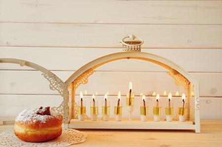 hanukka: Selective focus image of jewish holiday Hanukkah with menorah (traditional Candelabra) and donuts