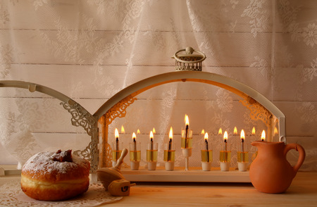 hanuka: Low key image of jewish holiday Hanukkah with menorah (traditional Candelabra), donuts and wooden dreidel (spinning top). Selective focus