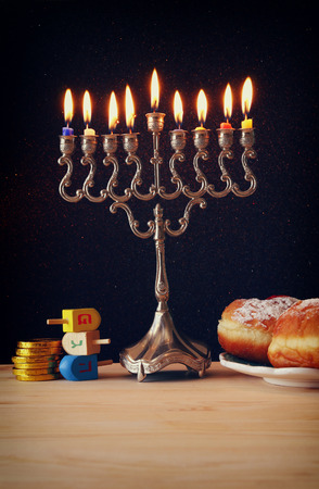 Image of jewish holiday Hanukkah with menorah (traditional Candelabra), donuts and wooden dreidel (spinning top)