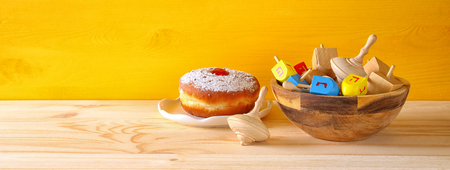 dreidels: Image of jewish holiday Hanukkah with wooden dreidels colection (spinning top) and donut on the table
