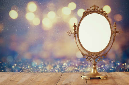 reflection: Old vintage oval mirror standing on wooden table.