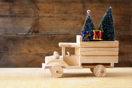 christmas toy: Wooden car carrying a christmas tree. Stock Photo