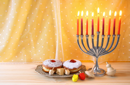 hanukah: Image of jewish holiday Hanukkah with menorah (traditional Candelabra), donut and wooden dreidel (spinning top)