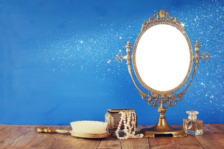 vintage objects: Old vintage oval mirror and woman toilet fashion objects on wooden table. Filtered image Stock Photo