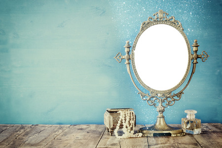 Old vintage oval mirror and woman toilet fashion objects on wooden table. Filtered image Standard-Bild