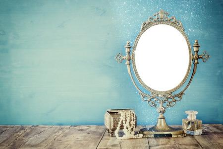Oude uitstekende ovale spiegel en vrouw wc mode-objecten op een houten tafel. gefilterde afbeelding