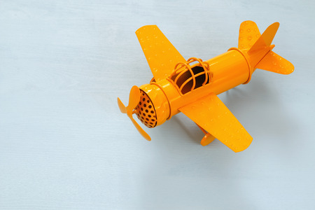 air plane: image of retro yellow metal toy airplane over wooden table.