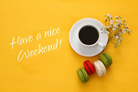 fin de semana: Vista superior de la taza de café con macarrón de colores o los macarrones en el fondo de madera. aplanada