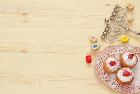 chanukiah: Image of jewish holiday Hanukkah with menorah (traditional Candelabra), donut and wooden dreidel (spinning top)